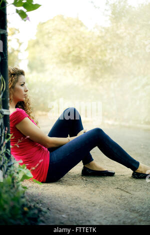 Casual young woman sitting in park - Stock Photo