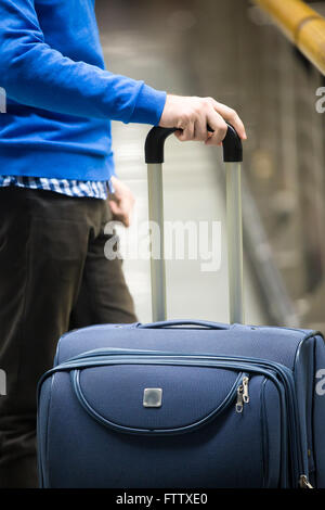 Close-up of young man hands holding suitcase in modern airport terminal. Travelling guy wearing smart casual style - Stock Photo