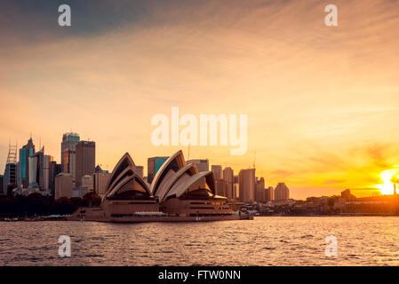 Sydney, Australia - November 11, 2015:  Opera House with Sydney city bihind at sunset. View from the ferry. - Stock Photo