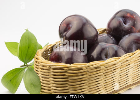 Close up photo of dark plums in a basket on white - Stock Photo