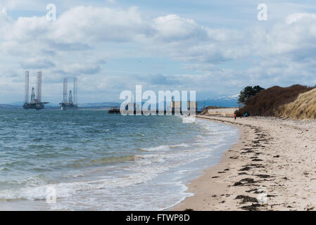 view of Cromarty Firth oil rigs from nigg beach - Stock Photo