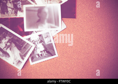 Vintage image of family photographs on corkboard - Stock Photo