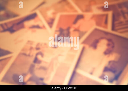 Defocused blur of scattered old family photographs against cork board - Stock Photo