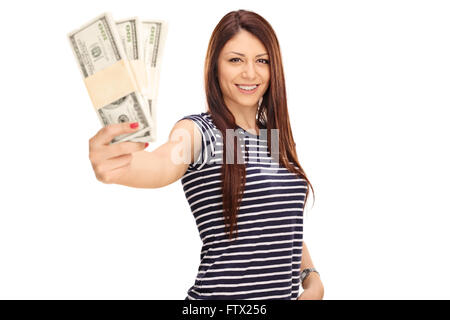 Cheerful young woman holding a few stacks of money and looking at the camera isolated on white background - Stock Photo