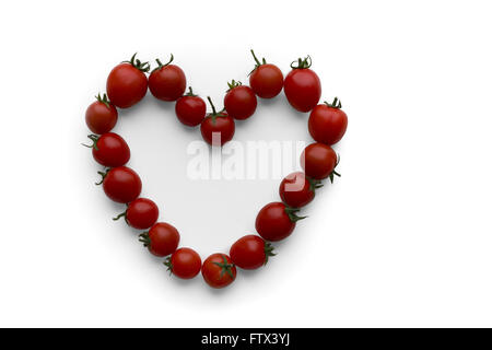 Love tomatoes - shape of love heart made out of red ripe cocktail tomatoes. Isolated on white. Valentine day concept - Stock Photo