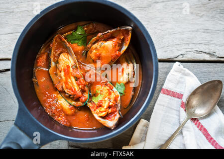 New zealand Mussels in Tomato and herbs sauce in a saucepan - Stock Photo