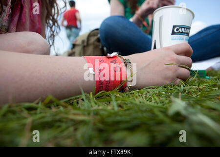 A large outdoor music festival and some of the crown take time out to lie in the grasss with a paper cup of beer - Stock Photo
