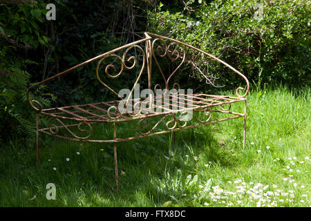 Old garden furniture made from iron etc sitting in an overgrown garden. - Stock Photo