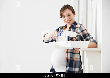 Portrait Of Pregnant Woman Decorating Nursery - Stock Photo