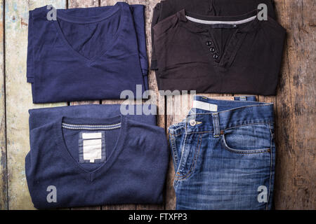 Various Man clothes collected on wooden background. Collection of men's T-shirts, jumper and jeans with blank labels
