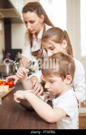 Small funny boy with his mother cooking with pots on the for Small childrens kitchen
