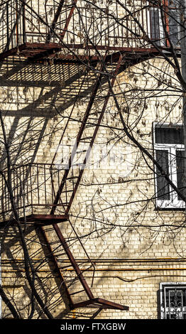 Old fire escape on facade of house in sun - Stock Photo