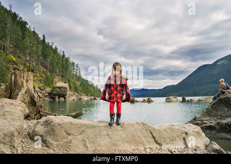 Young girl standing on rock in river valley - Stock Photo