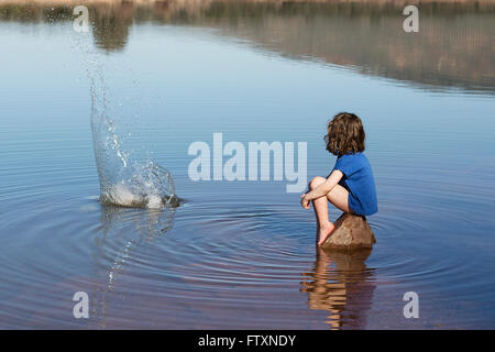 Girl sitting on a rock throwing stone in lake - Stock Photo