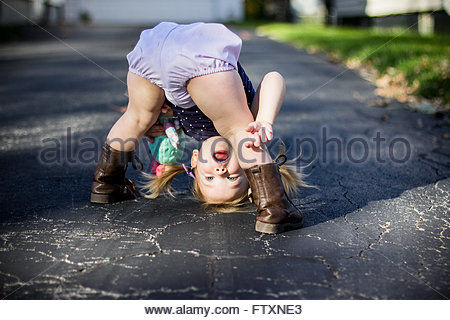 Girl bending over and looking through her legs upside down