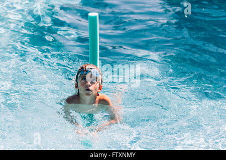 Boy swimming in swimming pool with water noodle - Stock Photo