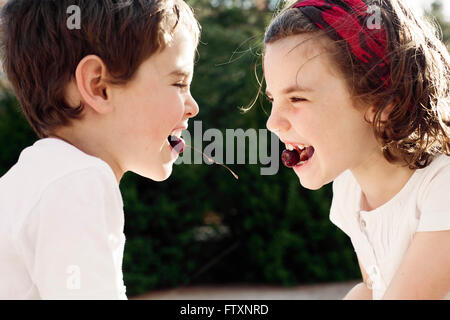 Boy and girl face to face eating cherries - Stock Photo