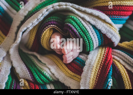 Close-up of baby's feet wrapped in a multi-colored blanket - Stock Photo