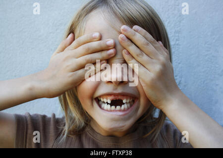 Boy with gap toothed smile with hands covering eyes - Stock Photo