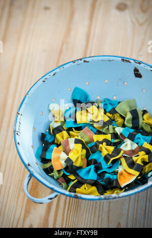 Butterfly Fantasia pasta. Farfalle pasta. Flavored coloured Pasta. Cooked Specialty pasta in a blue retro colander - Stock Photo