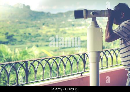 Man looking on mountains with binoculars, vintage toned photo - Stock Photo