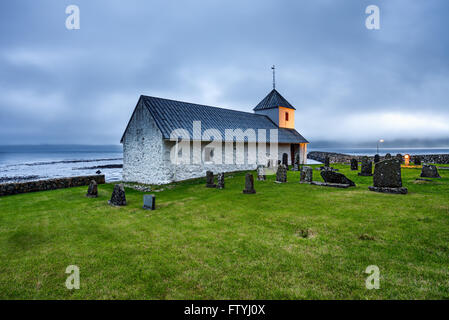 Small church with cemetery in the village of Kirkjubour, Faroe Islands, Denmark - Stock Photo