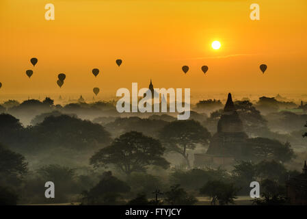 Scenic sunrise with many hot air balloons above Bagan in Myanmar. Bagan is an ancient city with thousands of historic - Stock Photo
