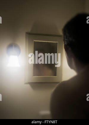 Man confronts his murky image in the mirror. - Stock Photo