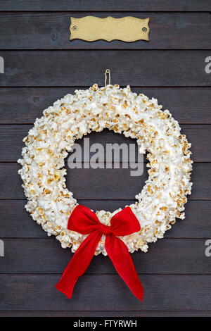 Popcorn wreath with red bow hanging on dark wooden door with name plate. - Stock Photo