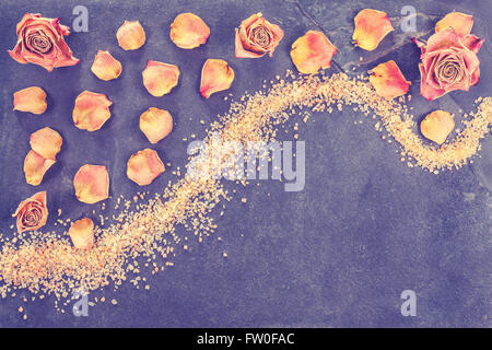 Vintage stylized dried roses and petals on slate, concept background with copy space. - Stock Photo