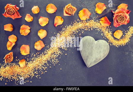 Vintage stylized dried roses and wooden heart on slate background. - Stock Photo
