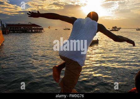 Local boys jumping off the Malecon into the sea next to the pier in Stone Town, Zanzibar, Tanzania - Stock Photo