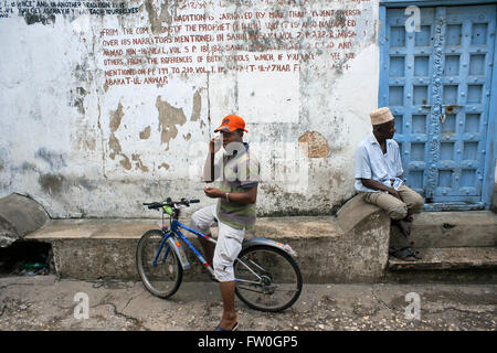 Local people and bicycle in one of Stone Town s maze of narrow streets, Zanzibar, Tanzania. - Stock Photo