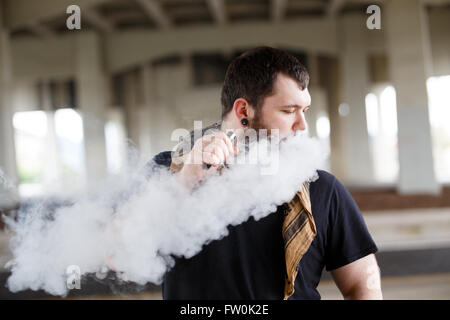 Urban lifestyle portrait of a man vaping in an urban environment with a custom vape mod device. - Stock Photo