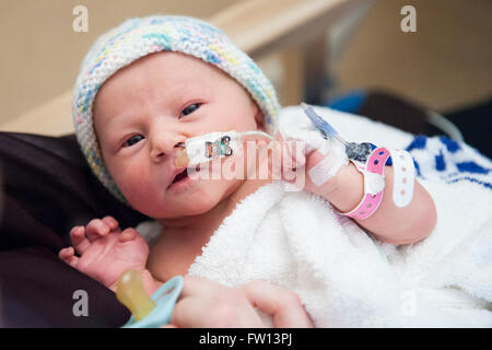 A closeup of a sick newborn baby girl being held in her mother's arms in a special care ward with a feeding tube - Stock Photo
