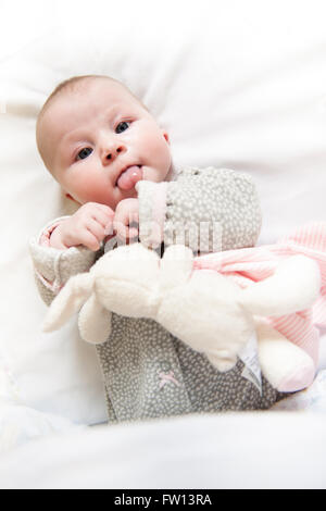 A cute newborn baby girl sticking out her tongue as she lies on white sheet with a  stuffed rabbit toy lying her - Stock Photo
