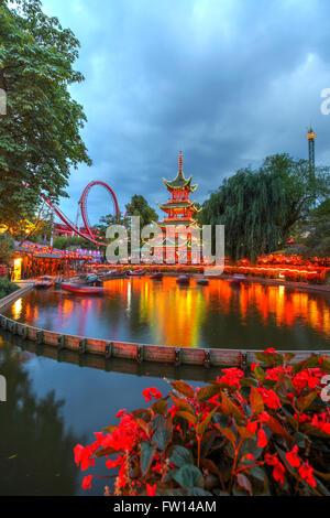 Dragon Boat lake and Dæmonen roller coaster in the background at Tivoli gardens, Copenhagen, Denmark - Stock Photo