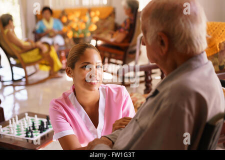 Old people in geriatric hospice: young attractive hispanic woman working as nurse takes care of a senior man on - Stock Photo