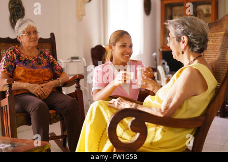 Old people in geriatric hospice: young attractive hispanic woman working as nurse helps a senior woman. She gives - Stock Photo