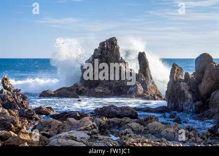 Wave crashing on large rocks sunny blue sky - Stock Photo
