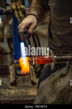 Glass artisan uses a hand torch to soften the piece he is working on. - Stock Photo