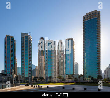Children playing in park in front of skyscrapers in down town Dubai. - Stock Photo