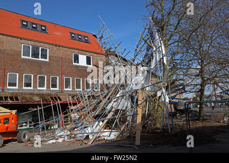 Collapsed scaffolding all bent and twisted laying at an angle where the wind has blown it away from the building - Stock Photo