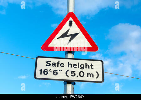 Live wire warning sign next to electrified train line - Stock Photo