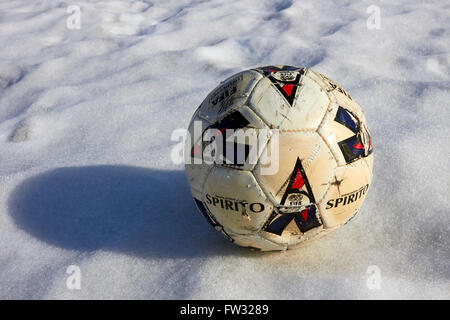worn-out football on snow - Stock Photo
