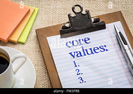 core values list on clipboard  with a pen, coffee and sticky notes against burlap canvas - business ethics and mission - Stock Photo