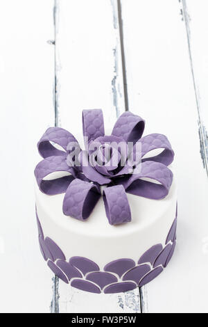 lovely decorated cake with a lilac bow on vintage background slightly above - Stock Photo
