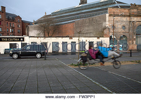 Boy in car watches as couple on two seater bicycle passes on Clyde St. by The Clutha closed and The Briggait, Glasgow, - Stock Photo