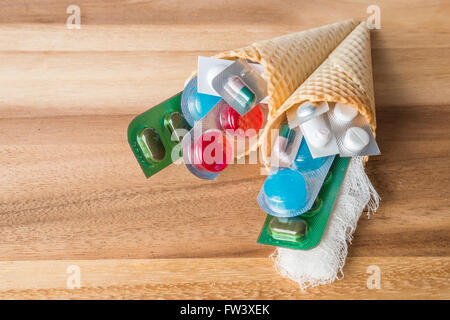 Mix of medicines and pills in wafer cones on wooden background - Stock Photo