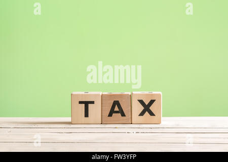 Tax sign made of wood on a green background - Stock Photo